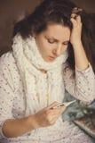 有温度计的病的女孩测量房子的温度 库存照片