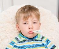 有温度计的病的男孩在放置在床上的嘴 库存图片