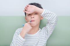 有温度计的病的男孩在嘴 库存照片