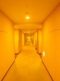 有温暖的光的长的旅馆走廊 库存图片