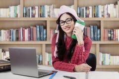 有温暖的衣裳的女孩在图书馆里 免版税库存照片