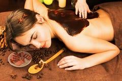 有温泉的沙龙的美丽的妇女巧克力疗法做法 库存图片