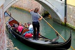 有游人和平底船的船夫的长平底船在威尼斯,意大利 库存图片