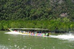 有游人的一条明亮的长的小船在美洲红树中的水浮动围拢由飞溅 侧视图 库存图片