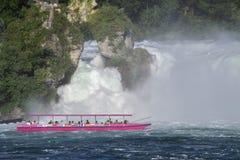 有游人的小船严密地倾吐对在莱茵河r的瀑布 免版税库存照片