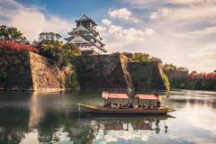有游人的旅游小船沿大阪城堡,大阪,日本护城河  库存照片