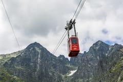 有游人的红色缆车在路线Skalnate pleso的Tatra山的- Lomnica峰顶 免版税库存照片