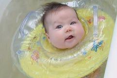 有游泳圈子微笑的新出生的婴孩 免版税库存图片