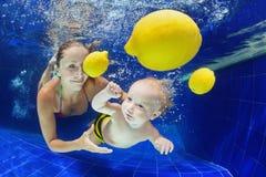 有游泳在水面下在水池的母亲的小孩 库存图片
