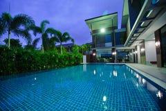 有游泳池的现代房子在晚上 库存图片