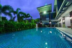 有游泳池的现代房子在晚上 免版税库存图片