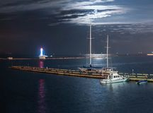 有游艇和灯塔的夜小游艇船坞 免版税库存照片