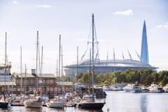 有游艇和Krestovsky体育场和Ga遥远的看法的小游艇船坞  库存照片