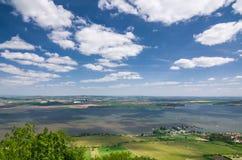 有湖、领域和蓝天的春天乡下与云彩 库存图片
