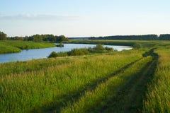 有湖和小山的绿色草甸 免版税库存图片