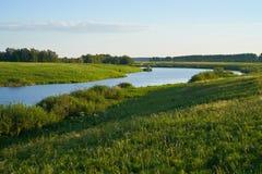 有湖和小山的绿色草甸 免版税库存照片