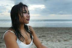有湿头发的年轻美丽的亚裔女孩在看在距离的日落海滩周道和沉思 免版税图库摄影