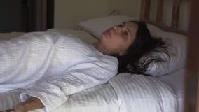 有湿头发的白种人妇女在善意的谎言在床上,讲话并且看照相机 影视素材
