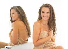 有湿长的头发的愉快的少妇在卫生间里 免版税图库摄影