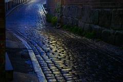 有湿鹅卵石的街道在晚上在一个老镇 库存图片