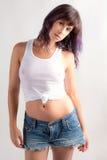 有湿头发的妇女在白色无袖衫和吉恩短裤 免版税库存照片
