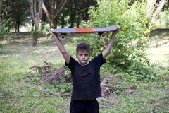 有滑板的一个少年 在手上拿着一只冰鞋 库存图片