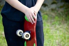 有滑板的一个少年 在手上拿着一只冰鞋 库存照片