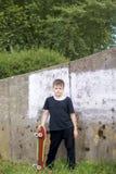 有滑板的一个少年 在手上拿着一只冰鞋 免版税库存图片