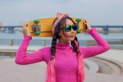 有滑板的明亮地加工好的女孩在城市 免版税库存照片