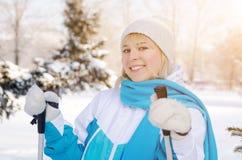 有滑雪杆的可爱的白肤金发的女孩在手上 免版税库存照片