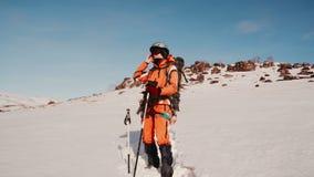 有滑雪杆的女孩登山人在看对边的雪调直他的玻璃并且享受多雪的风景 股票录像