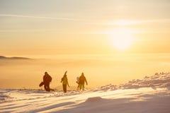 有滑雪的三个在日落山的朋友和雪板 免版税库存照片