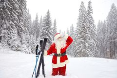 有滑雪的圣诞老人滑雪者在森林在圣诞节的冬天 免版税库存图片