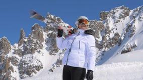有滑雪的女子滑雪者在她的肩膀敬佩自然秀丽在山的 库存照片