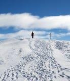 有滑雪的滑雪者在他的肩膀上升至多雪的山上面  库存图片