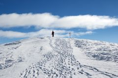 有滑雪的滑雪者在他的肩膀上升至山上面  免版税库存图片