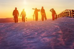 有滑雪的走到日落的朋友和雪板 免版税图库摄影