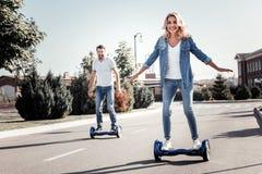 有满意的愉快的夫妇在自平衡的滑行车的乐趣骑马 免版税库存照片