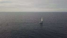 有漂浮在地平线背景鸟瞰图的蓝色海的白色风帆的豪华游艇 股票视频