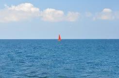 有漂浮沿天空蔚蓝背景的蓝色海的一个红色风帆的一条小船 免版税库存图片