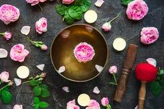 有漂浮的西藏唱歌碗上升了里面 灼烧的蜡烛、茶玫瑰色花和瓣在黑石背景 Medita 图库摄影