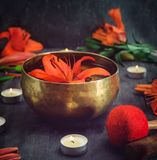 有漂浮的西藏唱歌碗在荷花里面 特别棍子、灼烧的蜡烛、百合花和瓣在黑色求爱 免版税图库摄影