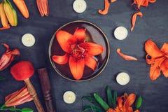 有漂浮的西藏唱歌碗在荷花里面 特别棍子、灼烧的蜡烛、百合花和瓣在黑色求爱 库存图片