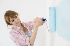 有漆滚筒的美丽的妇女绘画墙壁 免版税库存照片