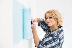 有漆滚筒的美丽的妇女绘画墙壁 免版税图库摄影