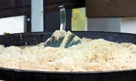 有漏杓匙子的大德国泡菜平底锅 德国食谱 免版税库存图片