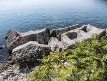有漏洞的被破坏的石块城堡墙壁在海水顶视图 库存照片