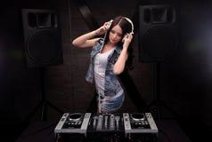 有演奏在搅拌器的白色耳机的Dj音乐与光束作用 在背景的扩音器 免版税库存照片