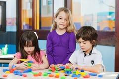 有演奏块的朋友的女孩在幼儿园 免版税图库摄影