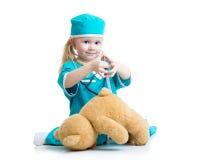 有演奏玩具的医生衣裳的儿童女孩 免版税库存图片